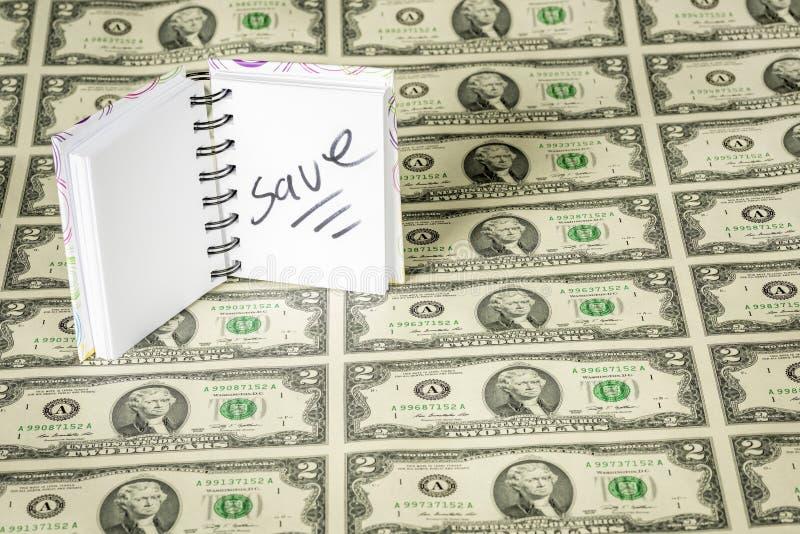 Litet block av papper med den skriftliga räddningen och pengar fotografering för bildbyråer