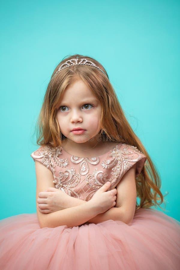 Litet Caucasian kvinnligt barn i rosa klänning med styggt och res royaltyfri bild
