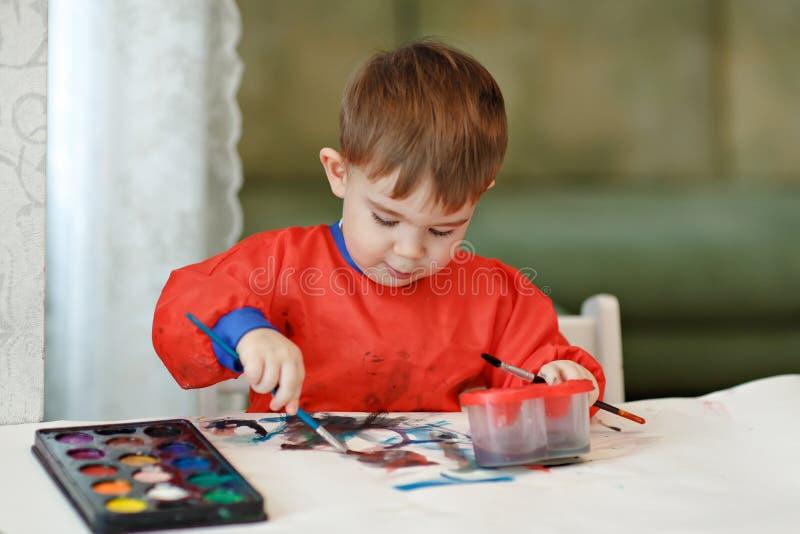 Litet charma behandla som ett barn pojken i en röda färgad målarfärgsittin för ämbetsdräkt attraktioner arkivbilder