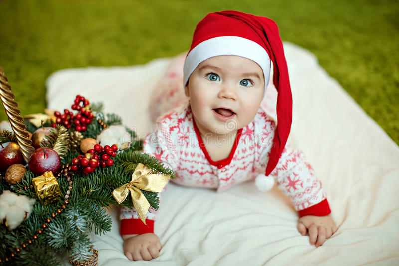 Litet charma behandla som ett barn pojken i röda jultomtenhattar och pyjamas med snowf royaltyfri foto