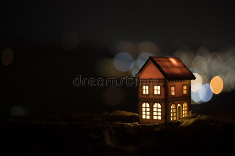 Litet dekorativt hus, härlig festlig stilleben, gulligt litet hus på natten, bakgrund för bokeh för nattstad verklig, lycklig vin arkivfoto