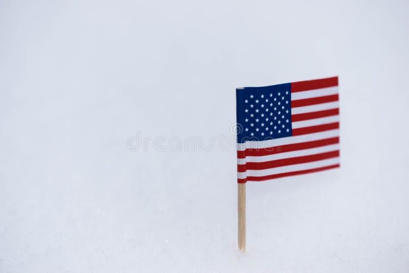 Litet enigt tillstånd av den Amerika flaggan som göras från papper med brun tandpetare på vit snöbakgrund arkivbilder