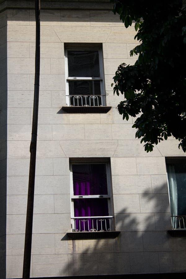 Litet fönster i gammal arkitekturbyggnad arkivfoto