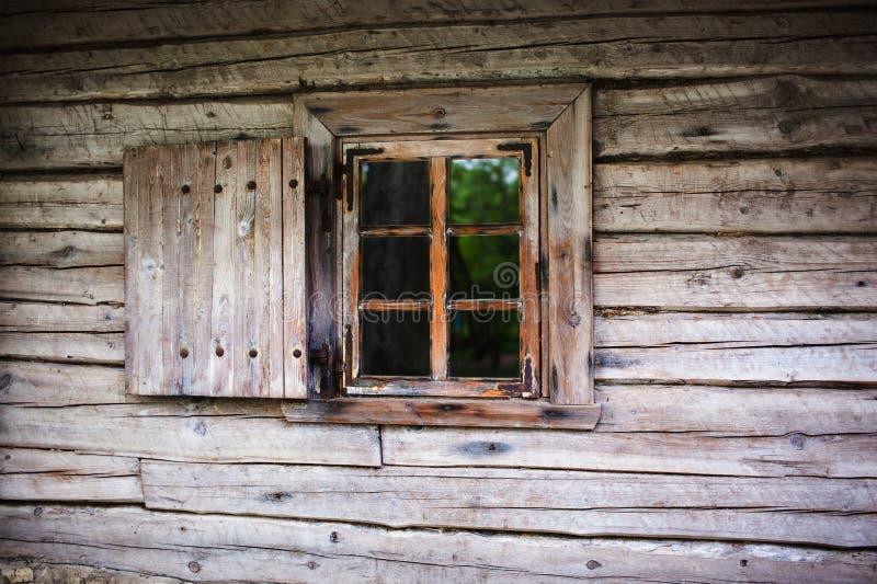 Litet fönster i väggen av ett gammalt trähus arkivfoton