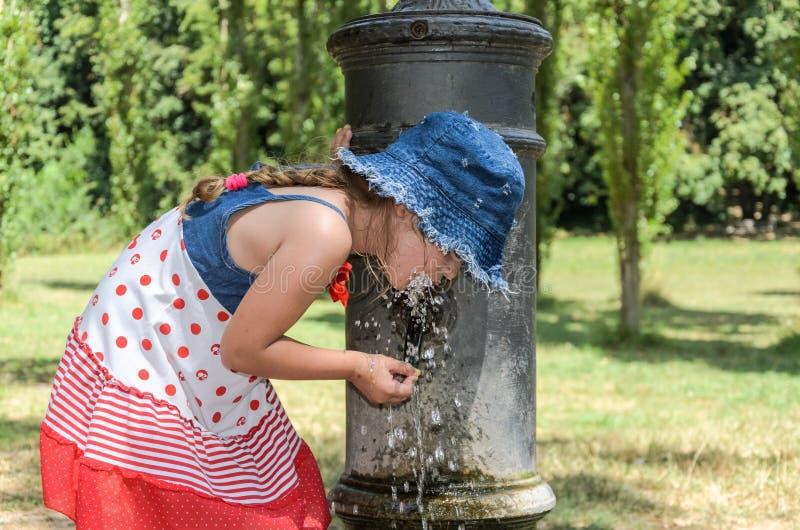 Litet förtjusande behandla som ett barn flickadrinkvatten från den dricka springbrunnen av den roman näsan på gatorna av Rome arkivfoto