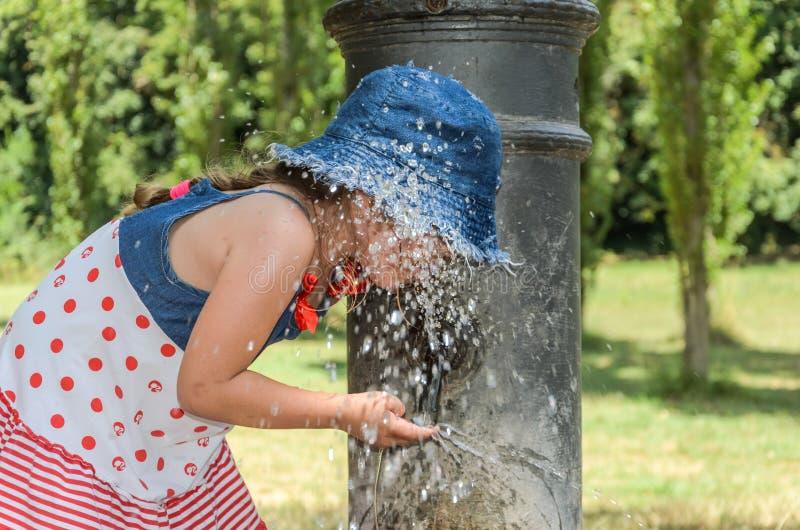 Litet förtjusande behandla som ett barn flickadrinkvatten från den dricka springbrunnen av den roman näsan på gatorna av Rome arkivbilder
