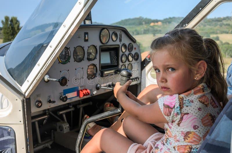 Litet förtjusande flickabarn - pilot på styrhjulet av ett ljust flygplan royaltyfri foto