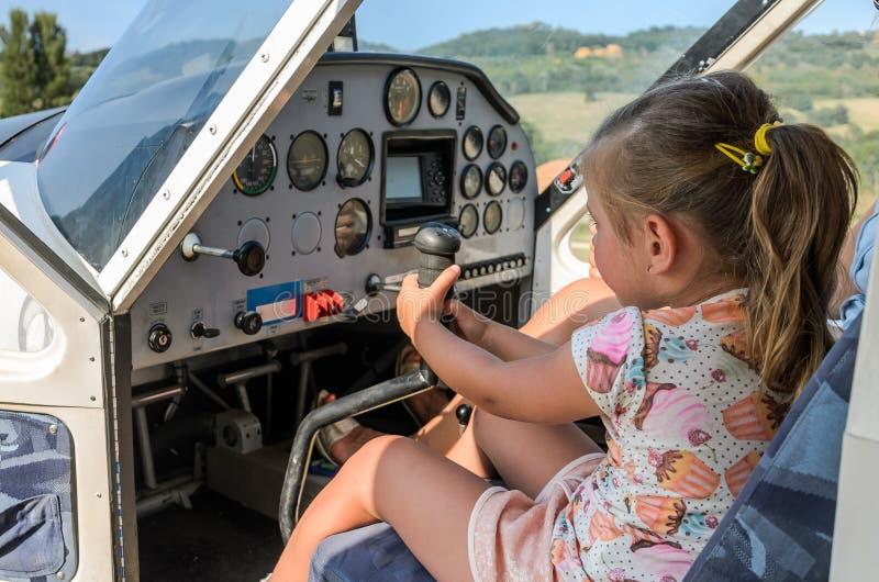 Litet förtjusande flickabarn - pilot på styrhjulet av ett ljust flygplan arkivfoton