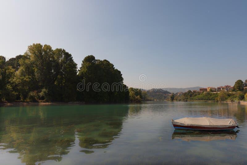 Litet fartyg i en sjö under en blå himmel arkivfoton
