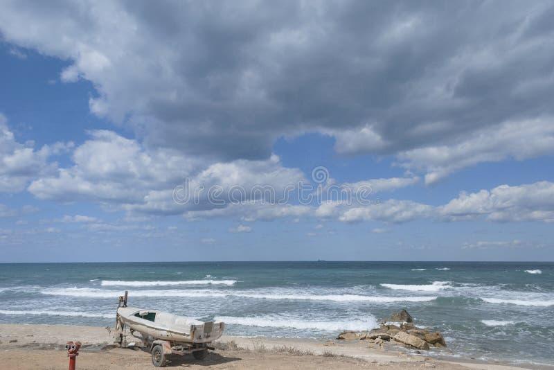 Litet fartyg och bränning på stranden nära Haifa royaltyfri fotografi