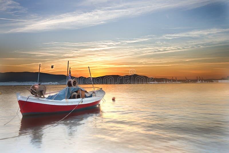 Litet fartyg på ett hav på solnedgången arkivbilder