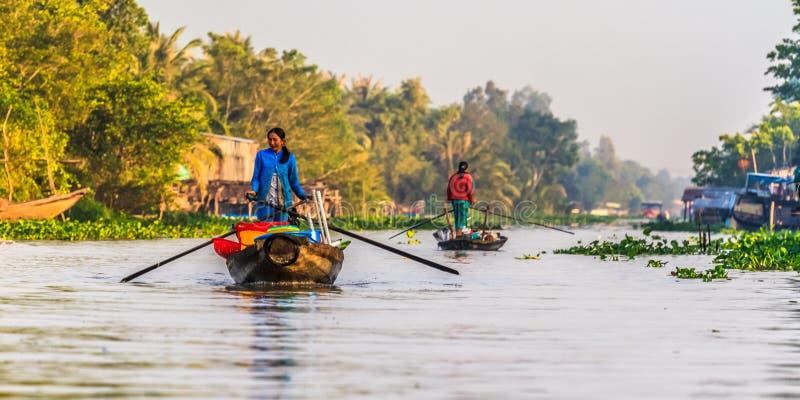 Litet fartyg som transporterar folk f?r att g? och tillbaka till den sv?va marknaden i Mekong River, Vietnam royaltyfria bilder