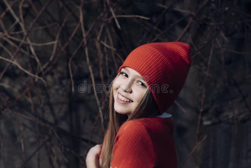 Litet flickaleende i r?d hatt, mode Barn som ler med utomhus- l?ngt blont h?r, sk?nhet Ungemodetrend och stil royaltyfri fotografi