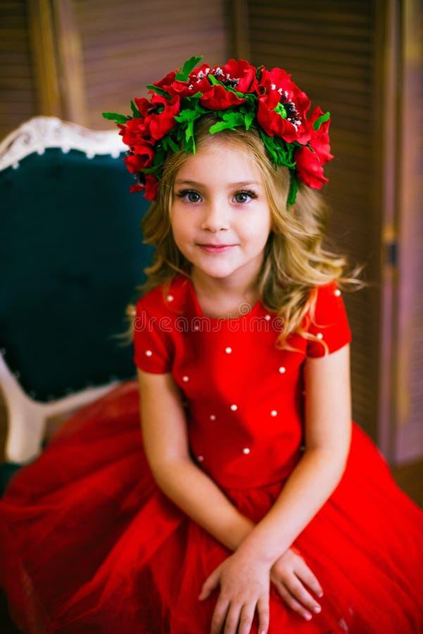 Litet flickaleende, mode Barn som ler med den blonda frisyren i röd klänning Begrepp f?r sk?nhetsalong Haircare frisör royaltyfri fotografi