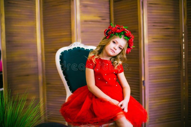 Litet flickaleende, mode Barn som ler med den blonda frisyren i röd klänning Begrepp f?r sk?nhetsalong Haircare frisör royaltyfria bilder