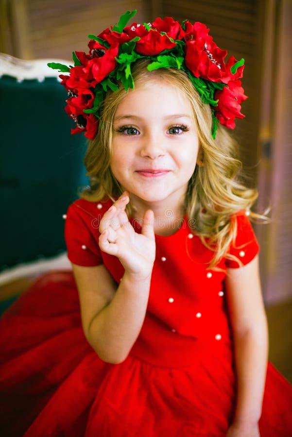 Litet flickaleende, mode Barn som ler med den blonda frisyren i röd klänning Begrepp f?r sk?nhetsalong Haircare frisör royaltyfri bild