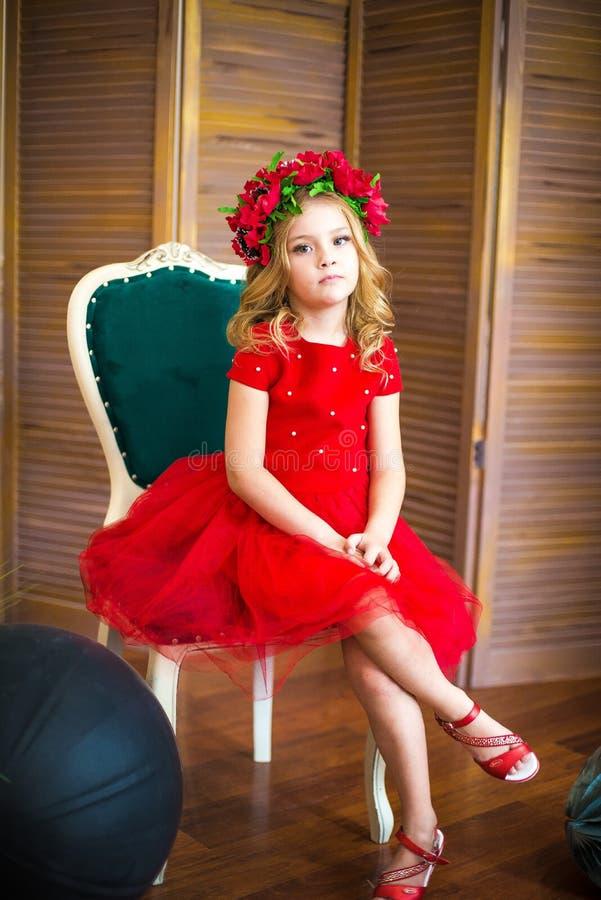 Litet flickaleende, mode Barn som ler med den blonda frisyren i röd klänning Begrepp f?r sk?nhetsalong Haircare frisör arkivbilder
