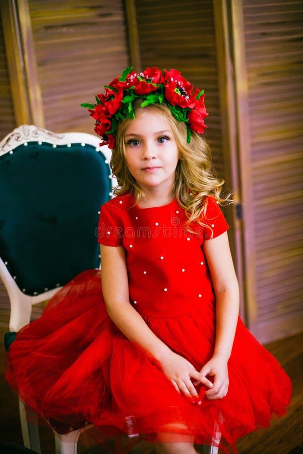 Litet flickaleende, mode Barn som ler med den blonda frisyren i röd klänning Begrepp f?r sk?nhetsalong Haircare frisör royaltyfri foto