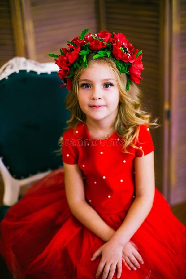 Litet flickaleende, mode Barn som ler med den blonda frisyren i röd klänning Begrepp f?r sk?nhetsalong Haircare frisör fotografering för bildbyråer