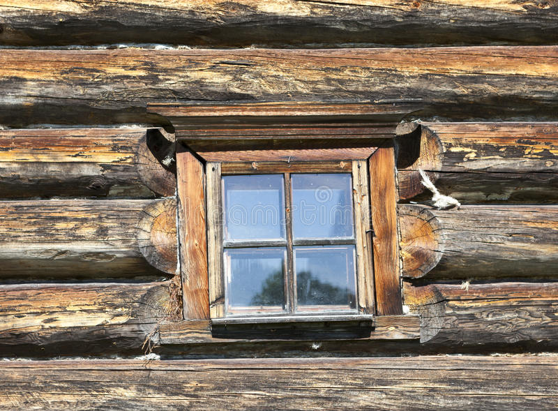 Litet gammalt fönster med exponeringsglas med en blå himmel på bakgrunden av träväggen av bygdjournalhuset arkivbild