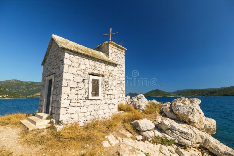 Litet gammalt kapell på ön, hav i bakgrunden royaltyfria foton