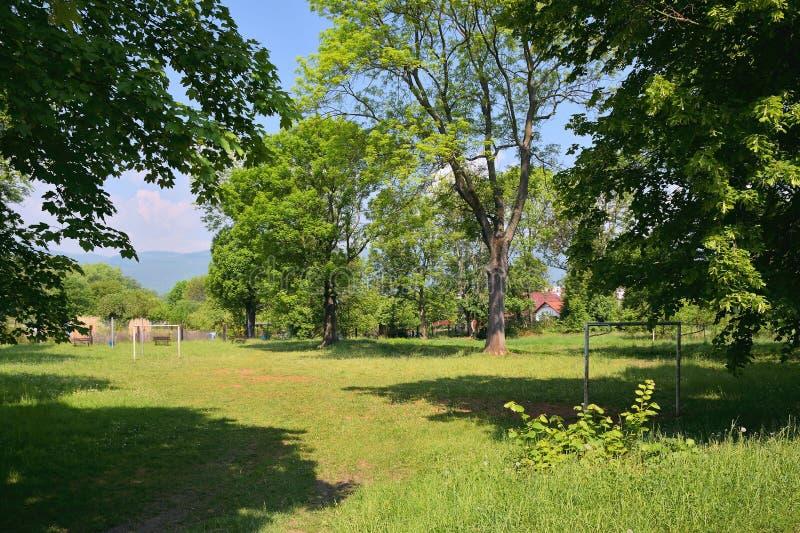 Litet gräs- fotbollfält mellan träd i tjeckisk stad av Chabarovice med malmberg på bakgrund i vår royaltyfria foton
