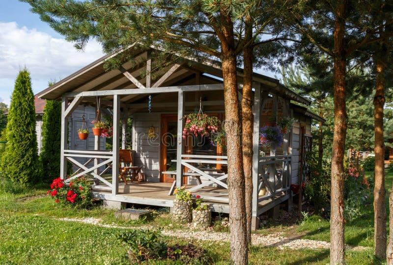 Litet grå färghus med trädäcket Främre gård med rabatt och gräsmatta royaltyfria foton