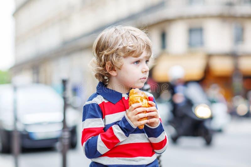 Litet gulligt barn på en gata av staden som äter den nya gifflet arkivbilder