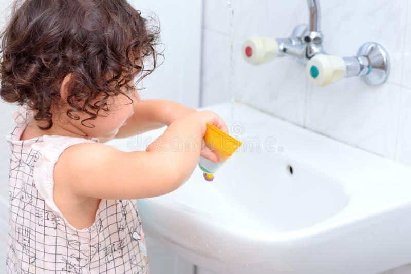 Litet gulligt behandla som ett barn flickan som gör ren hennes tänder med tandborsten i badrummet arkivbilder