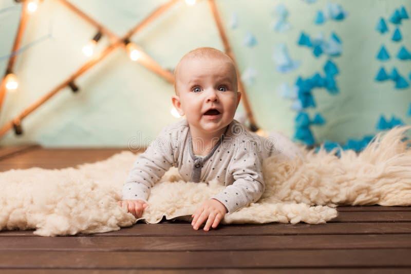 Litet gulligt behandla som ett barn pojkekrypning på golv bara i studio arkivfoton