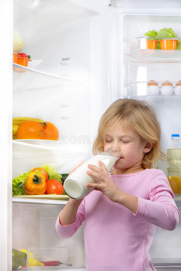 Litet gulligt dricka för flicka mjölkar nära den öppna kylen arkivbilder