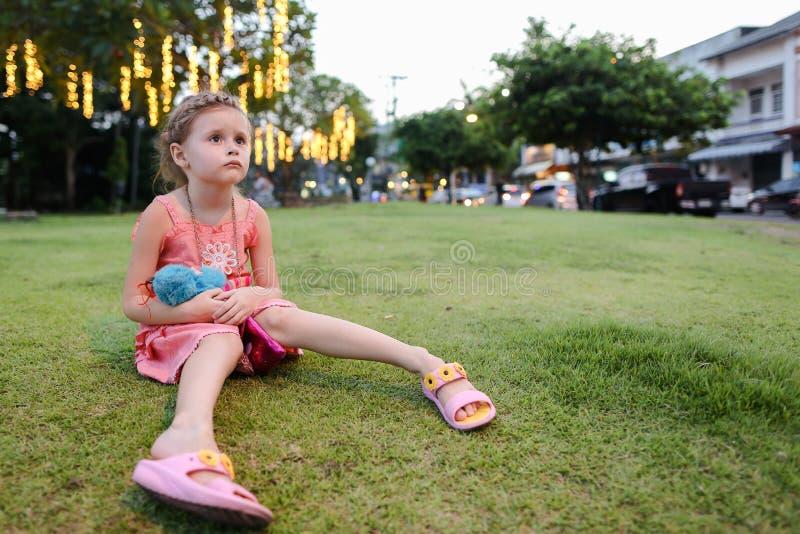 Litet gulligt flickasammanträde på gräsgräsmatta, byggnad på bakgrund fotografering för bildbyråer