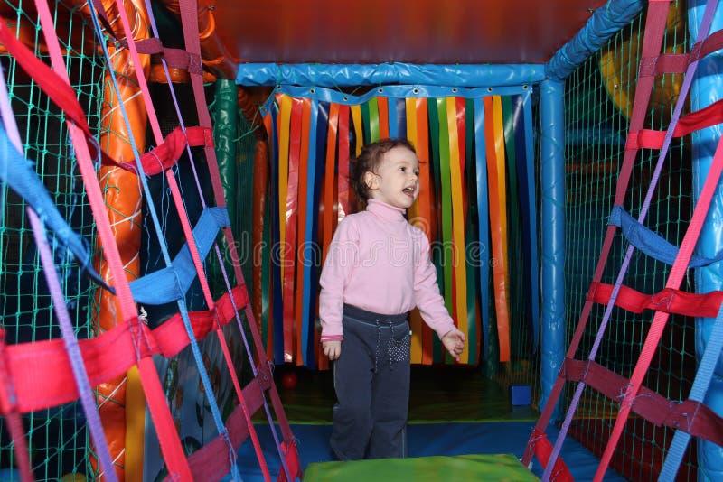 Litet gulligt lockigt behandla som ett barn flickan som spelar i barns en underhållningmitt i den modiga labyrinten Barnlekarna i fotografering för bildbyråer