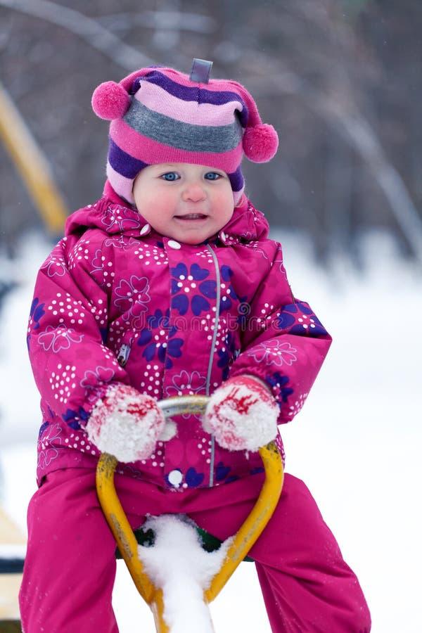 Litet gulligt lyckligt flickasammanträde på gunga arkivfoto