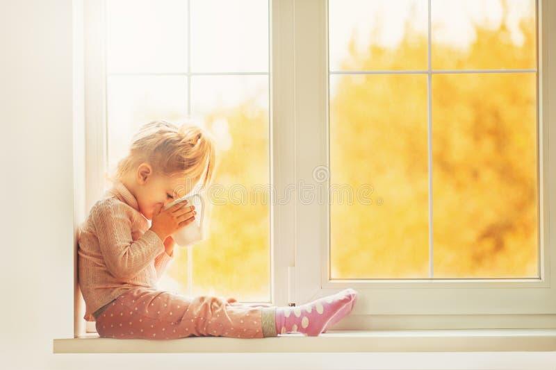 Litet gulligt ungeflickasammanträde vid den inomhus innehavkoppen för fönster av varm drinkkakao som tycker om höstskogbakgrund S royaltyfria foton
