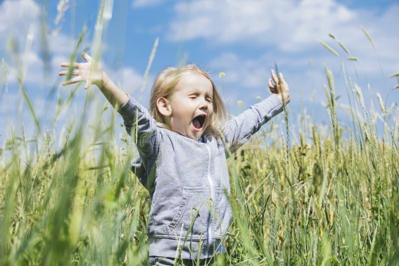 Litet härligt behandla som ett barn flickan utomhus i ett fält i den nya luften royaltyfri bild