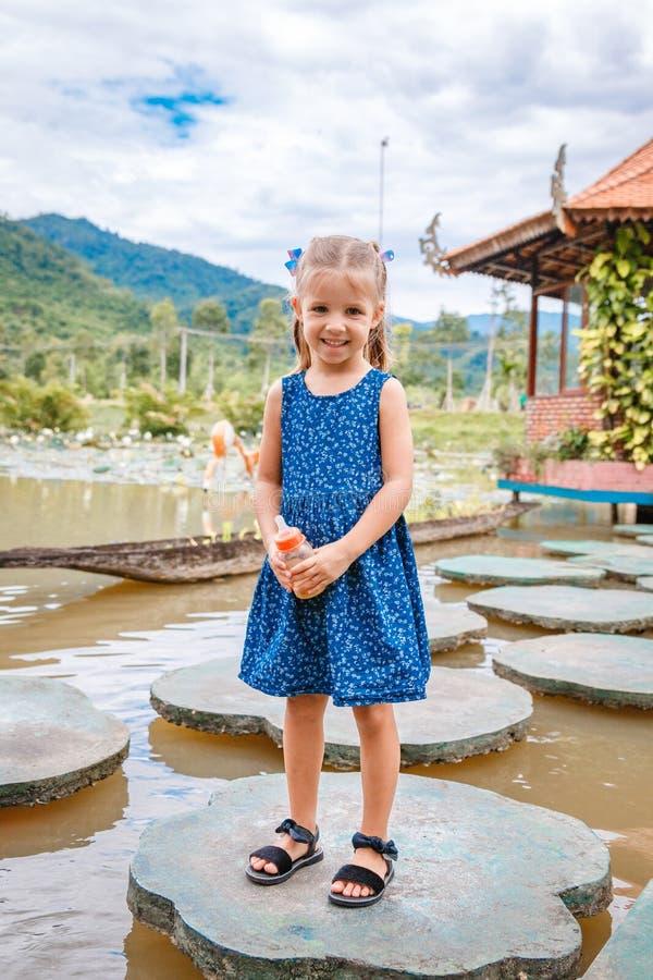 Litet härligt flickaanseende med en flaska av fiskmat i hand Yang Bay Vietnam arkivfoto