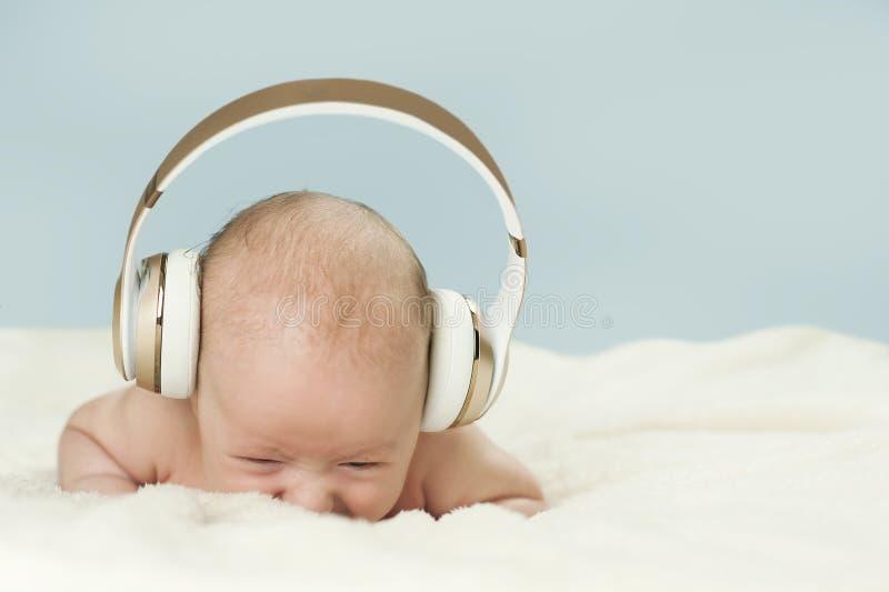 Litet härligt nyfött behandla som ett barn i stor hörlurar som lyssnar till musik som isoleras på blå bakgrund arkivbilder
