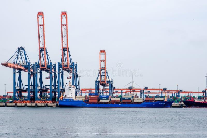 Litet havsbehållareskepp i en behållareterminal i porten av Rotterdam arkivfoto