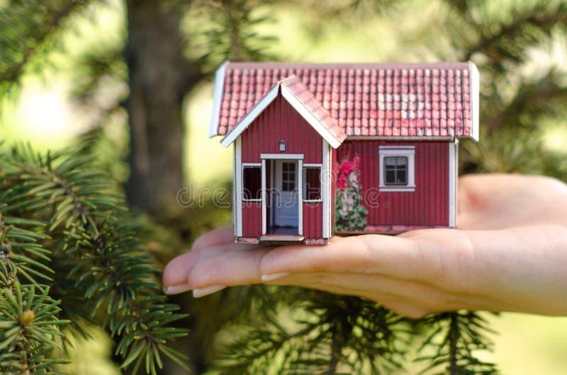 Litet hus i gräsplan för handnaturträd arkivfoto