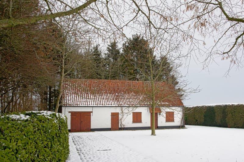 Litet hus i natur med insnöat den flemish bygden arkivbilder