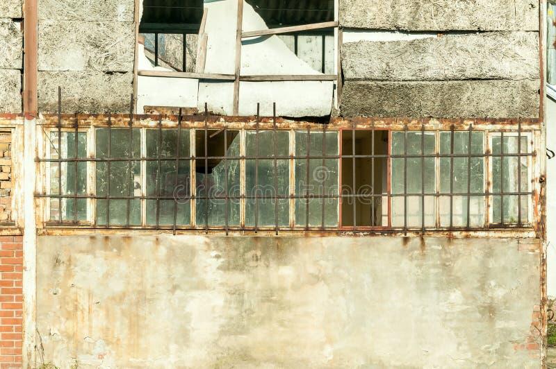 Litet hus nära byggnad med den skadade dörren och väggar med kulhål som används som improviserat dolt fängelse med stänger på fön arkivfoto