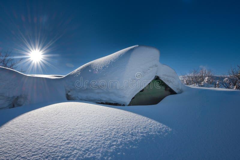 Litet hus som täckas med mycket snö efter tungt snöfall royaltyfria bilder