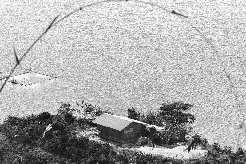 Litet hus under ön i en stor sjö royaltyfria bilder