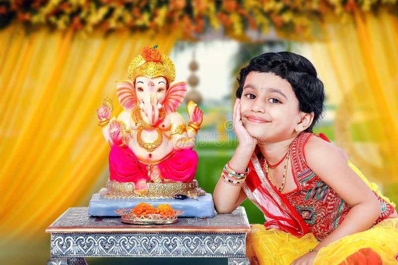 Litet indiskt flickabarn med ganesha och att be för lord, indisk ganeshfestival royaltyfri foto