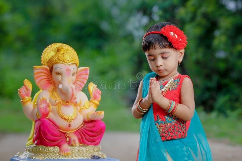 Litet indiskt flickabarn med ganesha och att be för lord, indisk ganeshfestival fotografering för bildbyråer