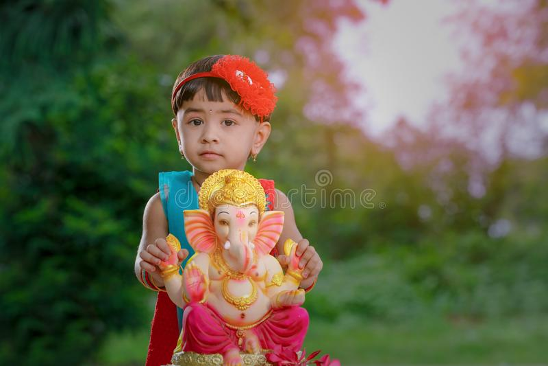 Litet indiskt flickabarn med ganesha och att be för lord, indisk ganeshfestival royaltyfri fotografi