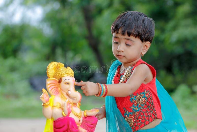 Litet indiskt flickabarn med ganesha och att be för lord, indisk ganeshfestival arkivbild