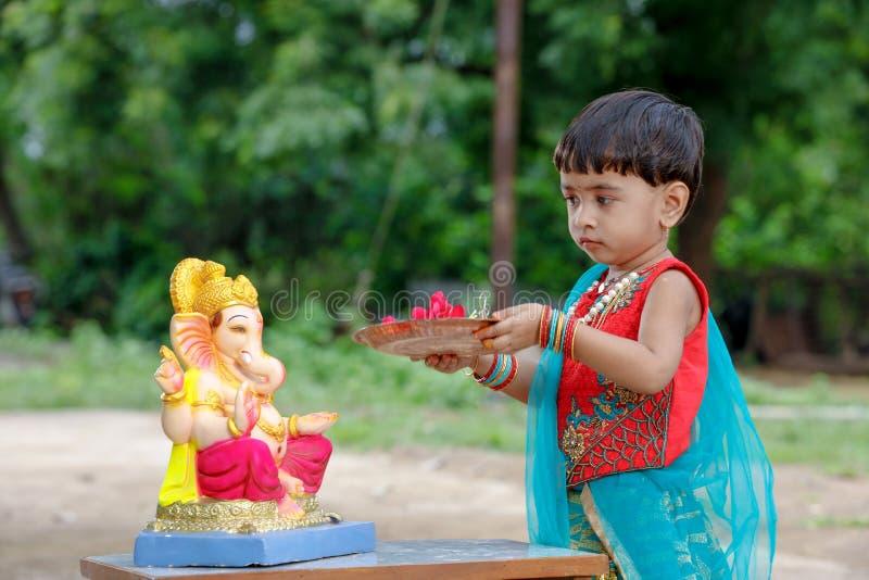 Litet indiskt flickabarn med ganesha och att be för lord, indisk ganeshfestival arkivfoto