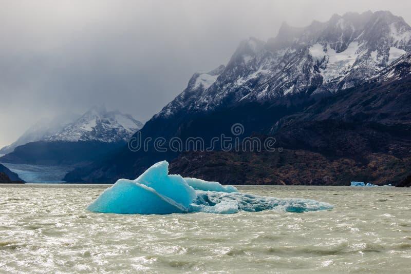Litet isberg som svävar under lågvatten i glaciärgrå färger, härlig bergskedja med insnöat bakgrunden Torres del Paine, Ch royaltyfria bilder